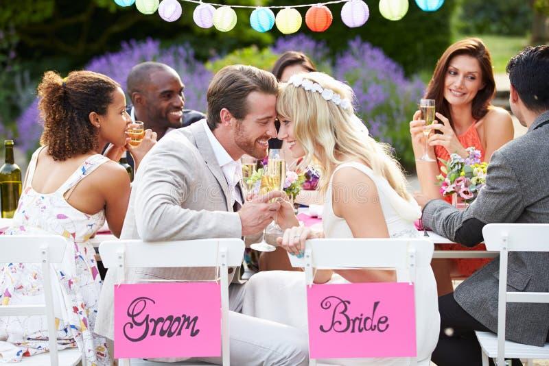Bruid en Bruidegom het Huwelijksontvangst van Enjoying Meal At royalty-vrije stock afbeeldingen