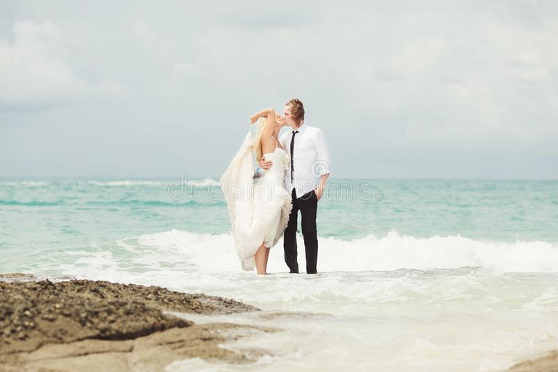 Bruid en bruidegom het kussen bij het overzees paar in liefde op verlaten strand royalty-vrije stock afbeelding