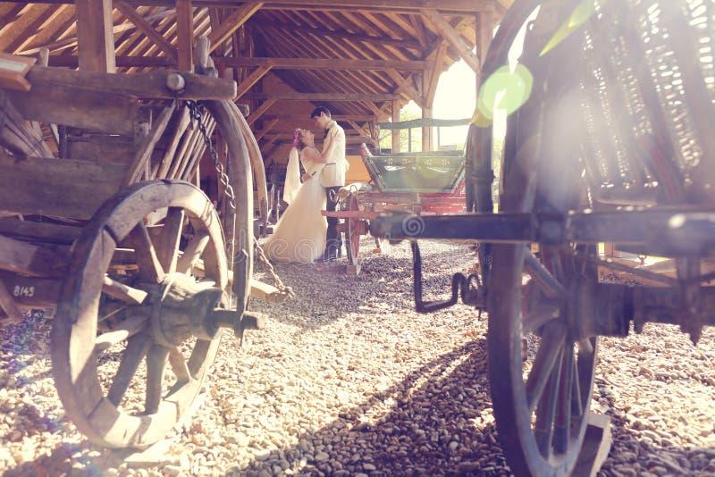 Bruid en bruidegom het kussen dichtbij houten vervoer stock foto's