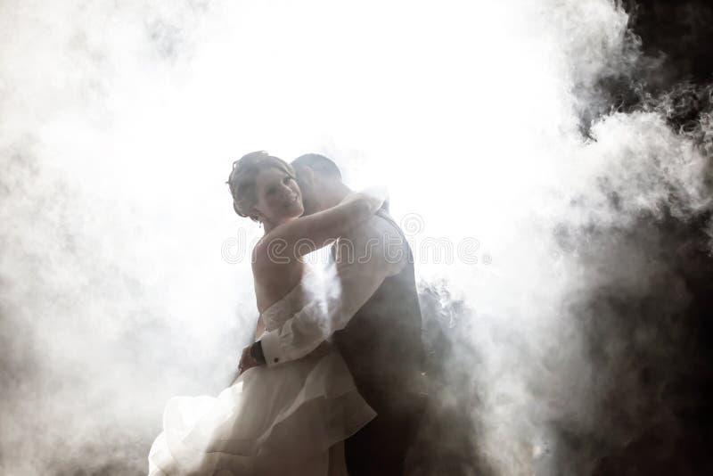 Bruid en Bruidegom het kussen in mist bij nacht royalty-vrije stock afbeelding