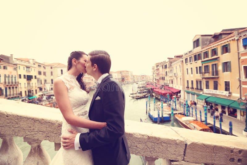 Bruid en bruidegom het kussen op een brug royalty-vrije stock foto's