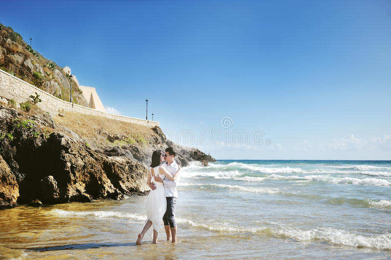 Bruid en bruidegom het kussen op het strand in huwelijksdag in Italië stock fotografie