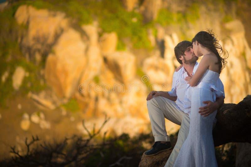 Bruid en bruidegom het kussen tegen de bergen bij zonsondergang stock afbeelding