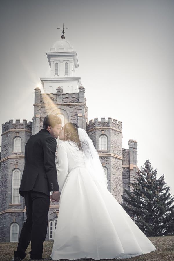 Bruid en bruidegom het kussen voor kerk royalty-vrije stock afbeelding