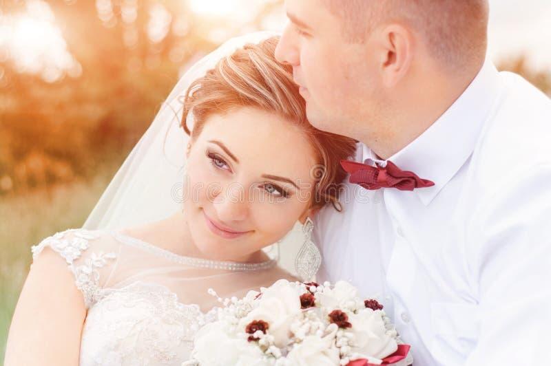 Bruid en bruidegom in het in openlucht binnen zonsonderganglicht Zachte embr stock afbeeldingen