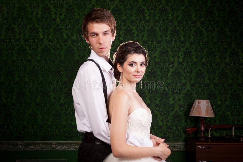 Bruid en bruidegom het stellen in uitstekende ruimte stock afbeelding