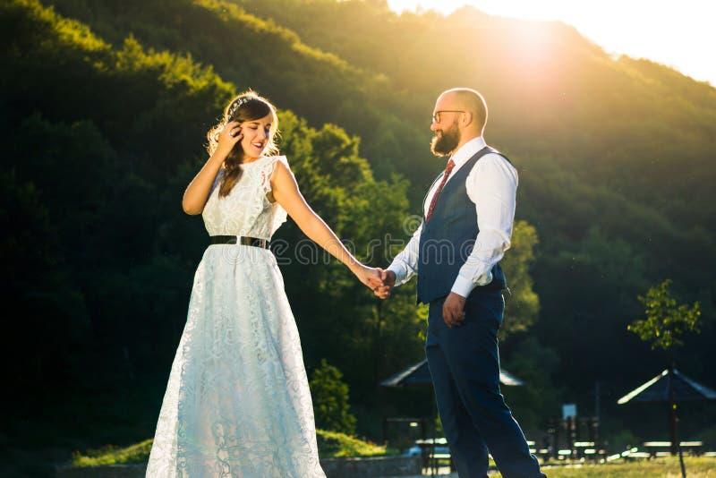 Bruid en Bruidegom Holding Hands bij Zonsondergang stock foto