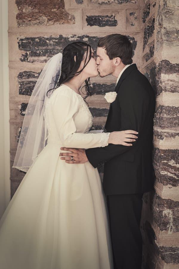 Bruid en Bruidegom Kissing door Bakstenen muur royalty-vrije stock afbeelding