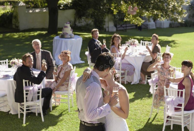 Bruid en Bruidegom Kissing In Garden royalty-vrije stock afbeeldingen