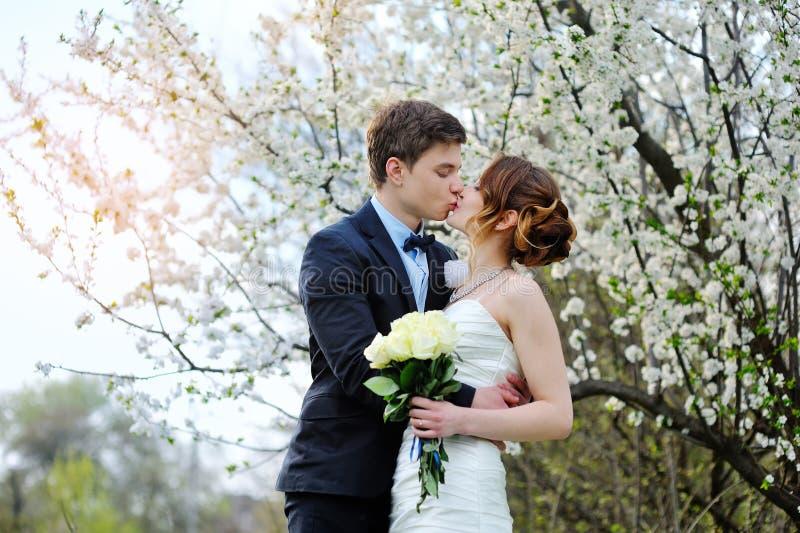 Bruid en bruidegom met een boeket van het lopen in het de zomerpark stock afbeeldingen