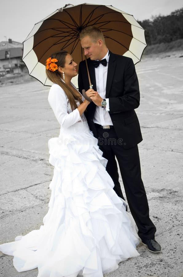 Bruid en bruidegom onder een paraplu royalty-vrije stock afbeelding