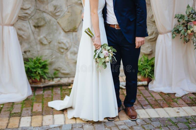 Bruid en bruidegom op de huwelijksceremonie Bruidholding bouguet van bloemen op de ceremonie royalty-vrije stock afbeeldingen