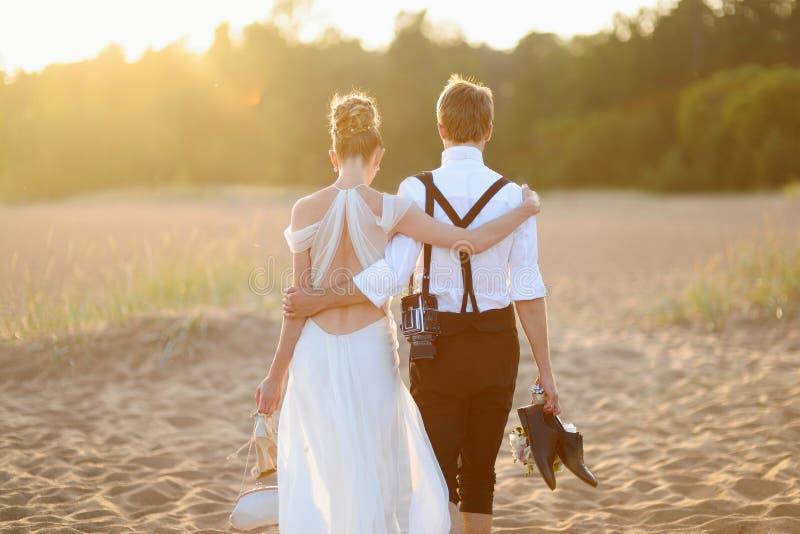 Bruid en bruidegom op een strand bij zonsondergang royalty-vrije stock afbeelding