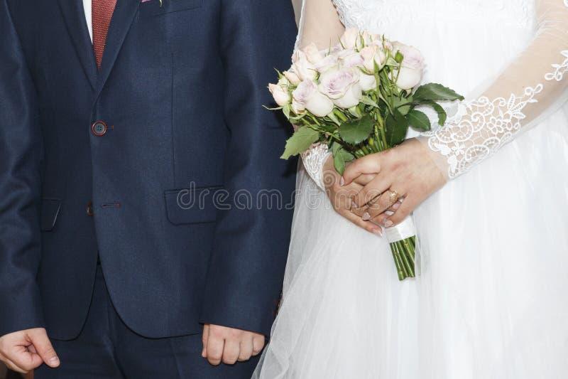 Bruid en bruidegom op huwelijksceremonie Boeket van rozen in handen van dame Mooie huwelijkskleding en elegant kostuum stock fotografie