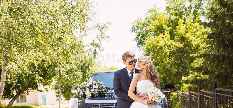 Bruid en bruidegom over de achtergrond van de huwelijksauto stock foto