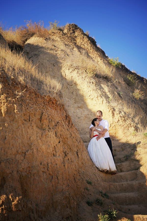 Bruid en bruidegom stellen samen openlucht in bergen in een huwelijksdag royalty-vrije stock foto's