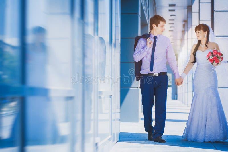 Bruid en bruidegom tegen een blauw modern gebouw royalty-vrije stock foto