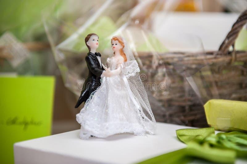 Bruid en bruidegom van suiker bovenop huwelijkscake die wordt gemaakt stock foto's