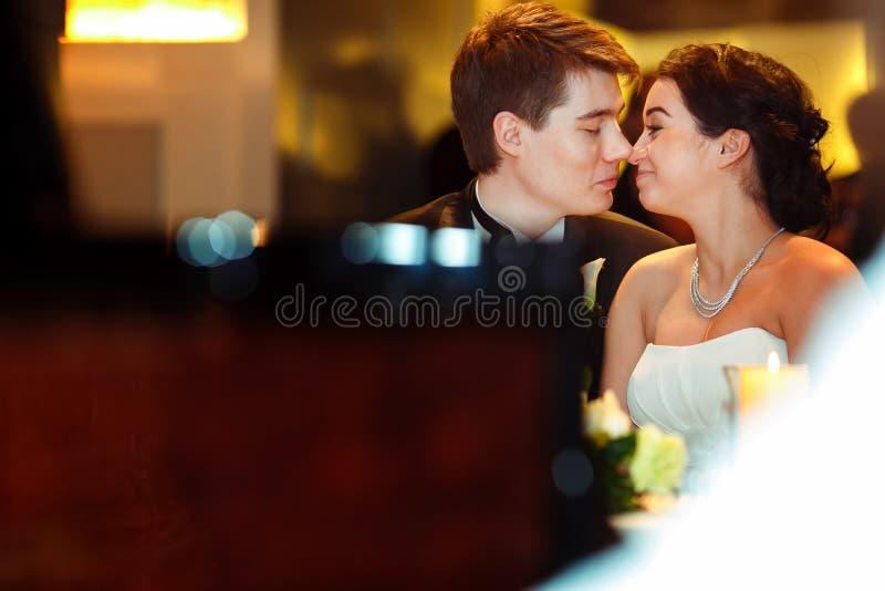 Bruid en bruidegomaanraking met neuzen die in het restaurant zitten stock afbeelding