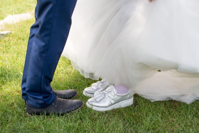 Bruid en bruidegombenen over het groene, gele gras stock afbeeldingen