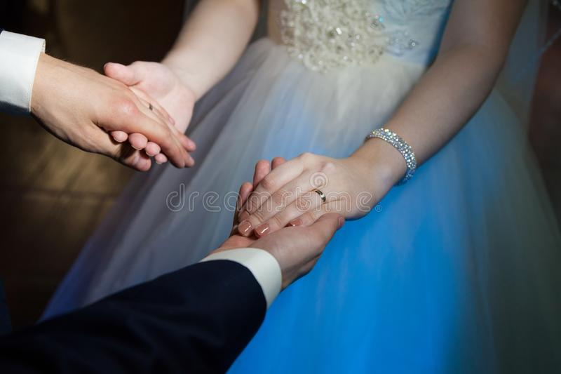 Bruid en bruidegomgreephanden tijdens de eerste dans, trouwringen stock fotografie