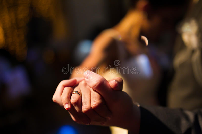 Bruid en bruidegomhanden tijdens de eerste dans stock foto