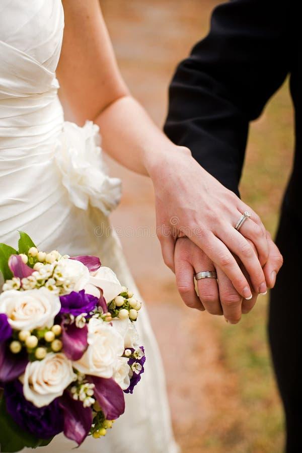 Bruid en bruidegomholdingshanden die hun trouwringen tonen royalty-vrije stock afbeelding