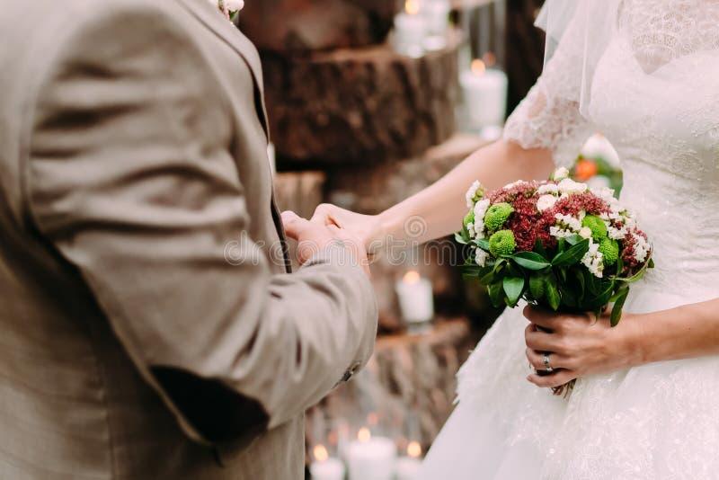 Bruid en bruidegomholdingshanden tijdens een huwelijksceremonie openlucht royalty-vrije stock foto's