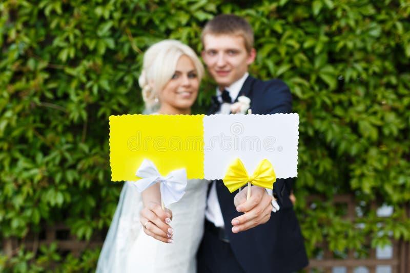 Bruid en bruidegomholdingsplaat in uw handen stock afbeelding
