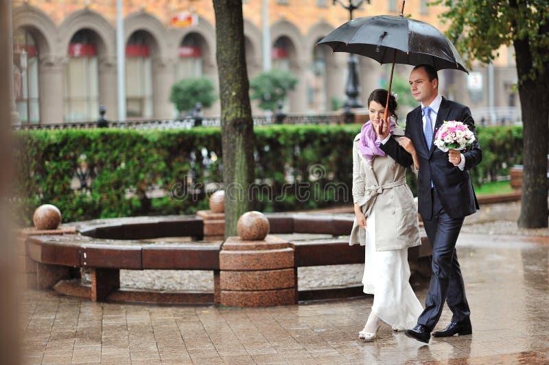 Bruid en bruidegompaar die samen in een regenachtige dag lopen stock afbeeldingen