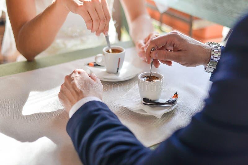 Bruid en bruidegomzitting in de koffie bij de lijst stock foto's