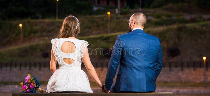 Bruid en bruidegomzitting door een meer bij nacht royalty-vrije stock foto