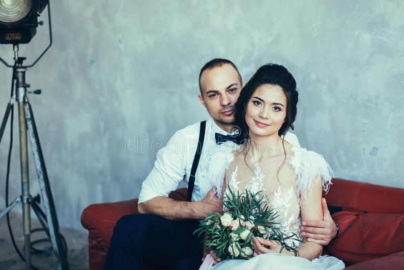 Bruid en bruidegomzitting op bank royalty-vrije stock foto