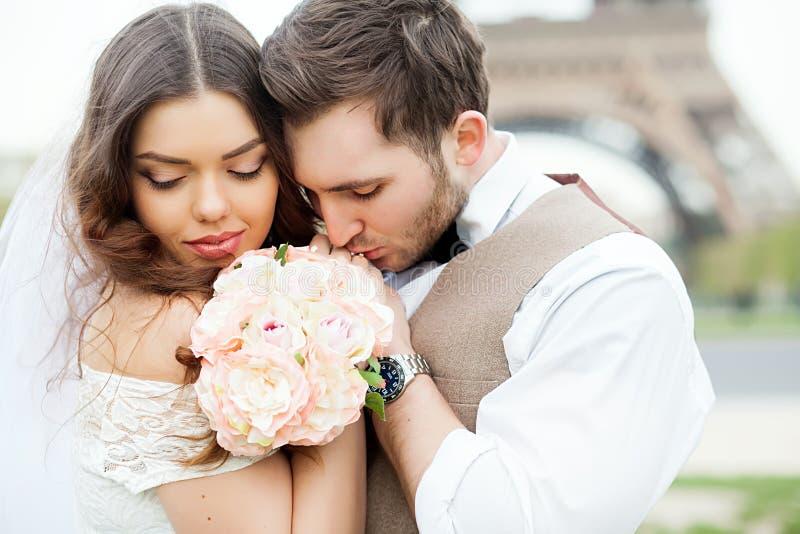 Bruid en bruidegomzitting op bank in park, holdingshanden van elkaar en boeket Bruidegom die zijn hoofd op bruid` s schouder houd stock foto