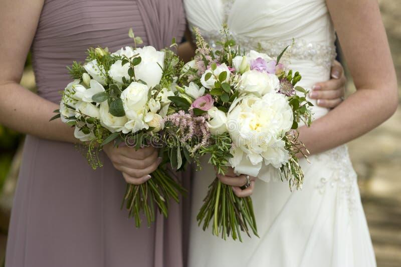 Bruid en bruidsmeisje met bloemen royalty-vrije stock afbeelding