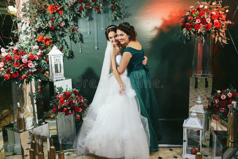 Bruid en bruidsmeisjeomhelzing onder de rode boeketten royalty-vrije stock afbeeldingen