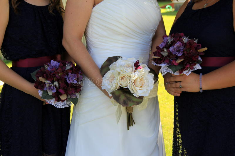 Bruid en bruidsmeisjes die bloemenboeketten houden royalty-vrije stock foto