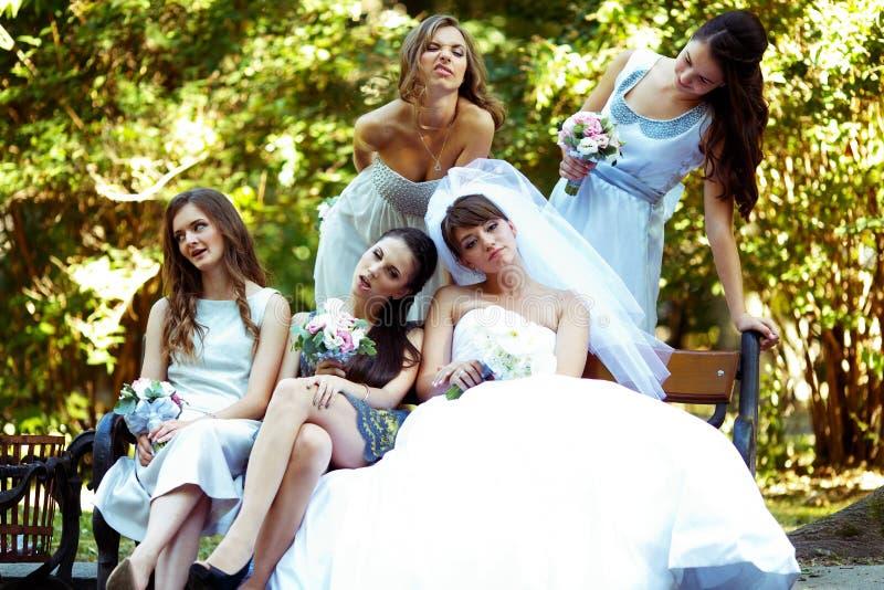 Bruid en bruidsmeisjesgrimaszitting op de bank in park stock foto's