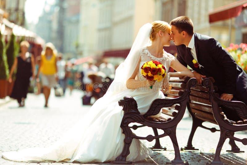 Bruid en fiancekuszitting op verschillende oude banken stock foto's