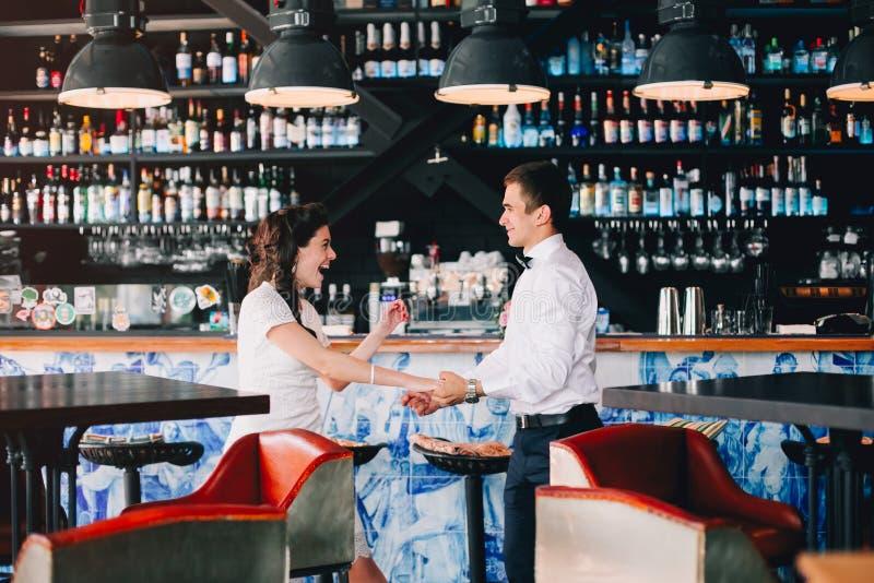 Bruid het glimlachen en lach terwijl bruidegom die met haar in de bar dansen Expressief en emotioneel huwelijkspaar royalty-vrije stock afbeelding