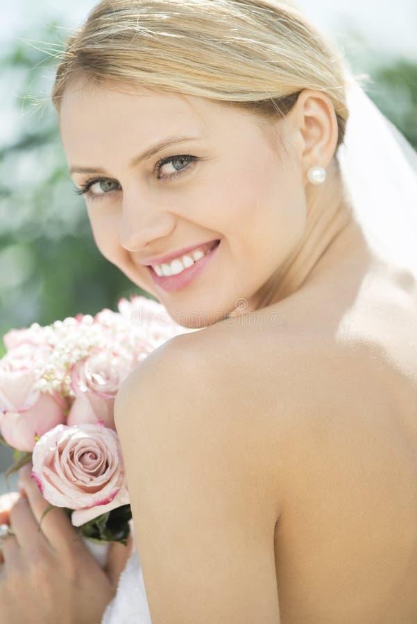 Bruid in het Rugloze Boeket van de de Holdingsbloem van de Huwelijkskleding stock afbeelding