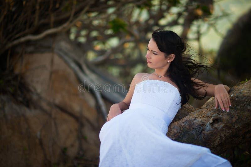 Bruid in huwelijkskleding die in de bergen in het midden van tropische bomen liggen royalty-vrije stock foto