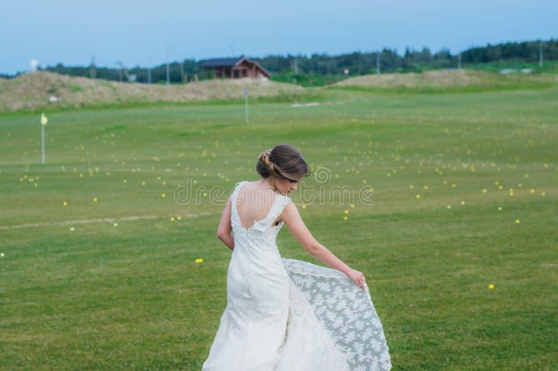 Bruid in huwelijkskleding op het groene gebied van de golfclub stock foto