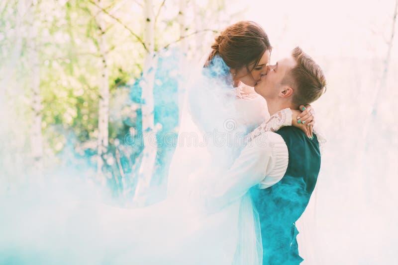 Bruid kussende bruidegom in turkooise rook op aard royalty-vrije stock afbeeldingen