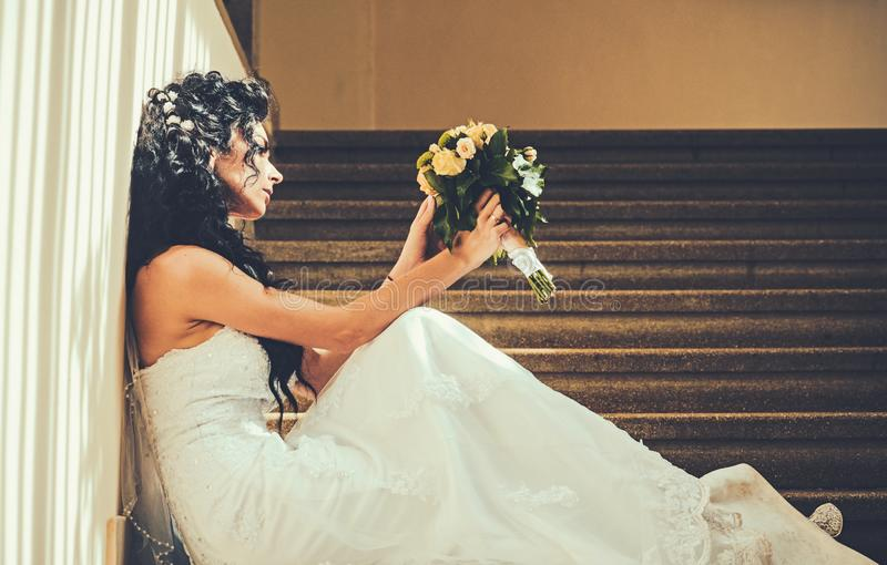 Bruid in manier witte kleding Sensuele vrouw met huwelijksboeket De vrouw met bloemen zit op trap Meisje met bruids stock afbeelding