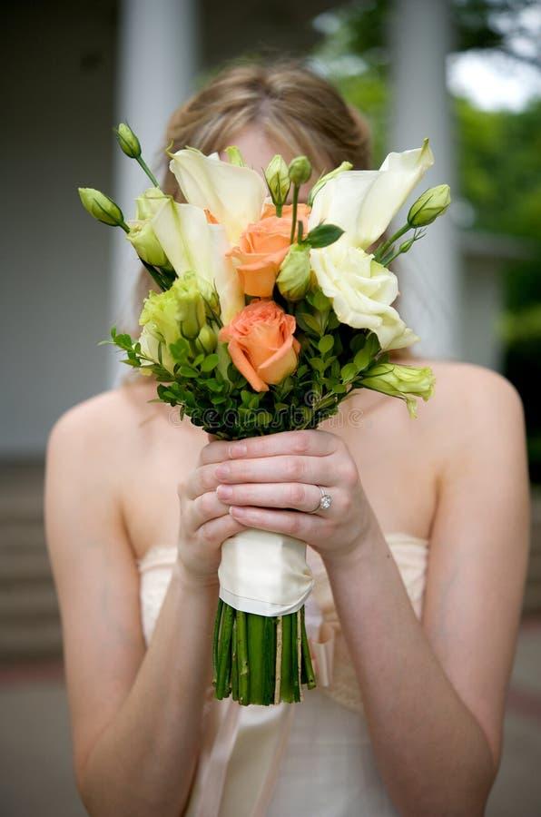 Bruid met boeket voor haar gezicht stock afbeelding