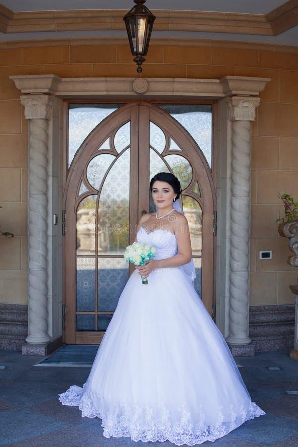 Bruid met een boeket op de achtergrond van de deur stock fotografie