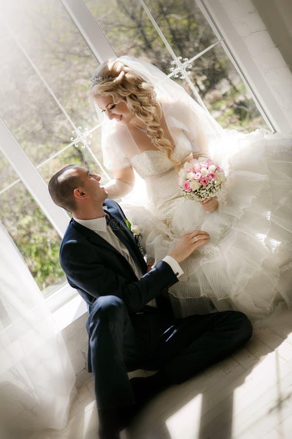 Bruid met een huwelijksboeket van rozen en de bruidegomzitting bij een venster stock afbeelding