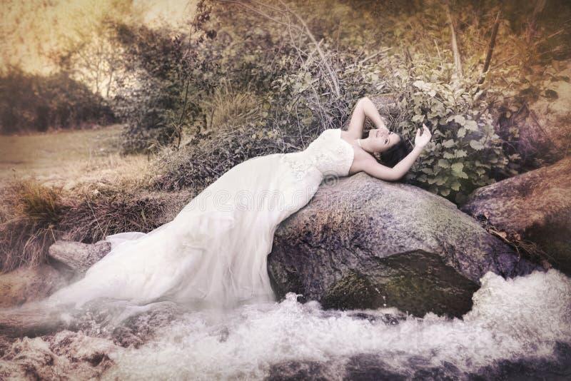 Bruid met lange toga dichtbij wateren royalty-vrije stock afbeelding