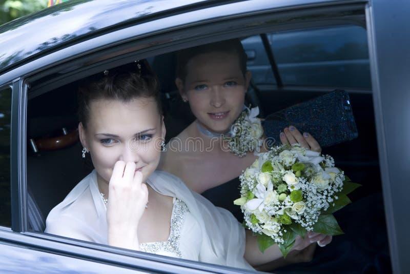 Bruid met meisje van eer in de auto royalty-vrije stock afbeeldingen